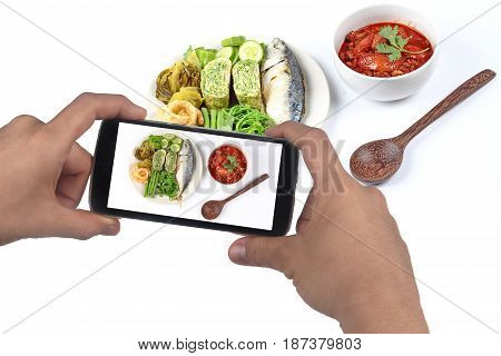 Use mobile phone to take photo Thai recipe as the spicy meat and tomato dipNam Prik Ong in Thaifor share in social network.