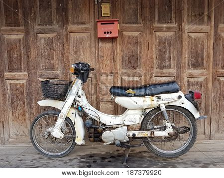 CHIANG RAI THAILAND - MAY 6 : old Yamaha motorcycle on wooden door background on May 6 2017 in Chiang rai Thailand.