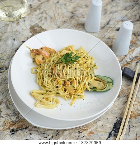 Flat egg noodles with seafood served in big white ceramic round plate with glass of white wine on marble table