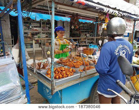 KAMPHAENG PHET THAILAND - MAY 6 : unidentified asian woman selling fried chicken in Nakhon Chum street market on May 6 2017 in Kamphaeng Phet Thailand.