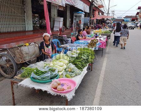 KAMPHAENG PHET THAILAND - MAY 6 : unidentified asian woman selling vegetables in Nakhon Chum street market on May 6 2017 in Kamphaeng Phet Thailand.