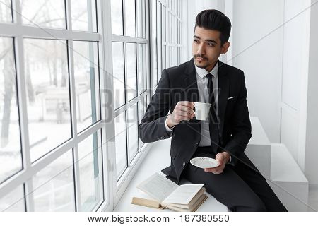 Thinking Businessman In Suit Sitting On Windowsill And Drinks Coffee.