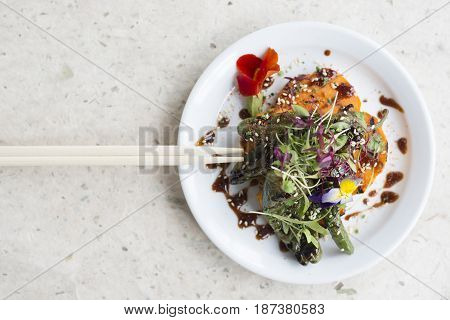 Overhead Of Vegetable Salad Meal On Round White Plate And Chopsticks