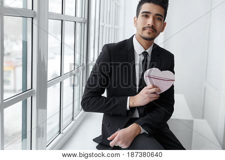Young businessman in love sitting on windowsill with gift in form of heart. Successful business concept