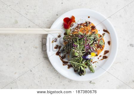 Chopsticks And Vegetable Salad Meal On Round White Plate