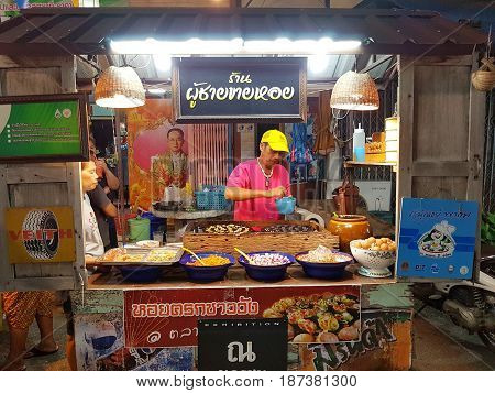 KAMPHAENG PHET THAILAND - MAY 6 : unidentified asian man with Thai traditional clothing selling oyster omelette in Nakhon Chum street market on May 6 2017 in Kamphaeng Phet Thailand.