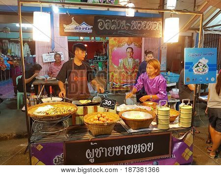 KAMPHAENG PHET THAILAND - MAY 6 : unidentified asian man with Thai traditional clothing selling fried oyster omelette in Nakhon Chum street market on May 6 2017 in Kamphaeng Phet Thailand.