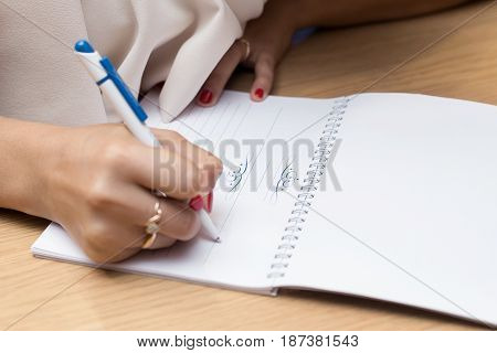 Hand With Pencil Writing In Notebook On Wooden Table
