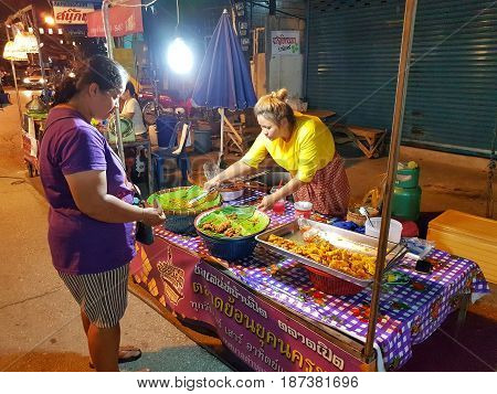KAMPHAENG PHET THAILAND - MAY 6 : unidentified asian woman with Thai traditional clothing selling fried snacks in Nakhon Chum street market on May 6 2017 in Kamphaeng Phet Thailand.