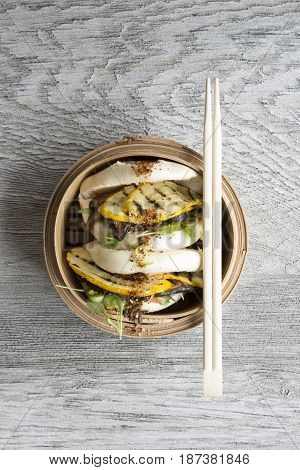 Overhead Of Chopsticks On Steamed Buns In Bamboo Steamer