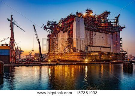 Oil rig under construction at night in Gdansk Poland.
