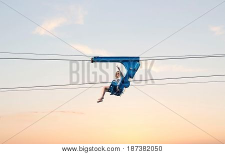 horizontal image of a young woman taking an air ride on a zip line in the early evening sun setting.