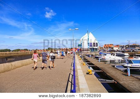 HEL POLAND - AUGUST 10 2015: People walking through in the port on the waterfront with many boat and sailboat in Hel. Hel is one of most famous cruise travel destinations in Poland.