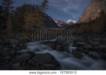 Mountain river in the background of autumn landscape and setting sun, Altai region, Siberia, Russia