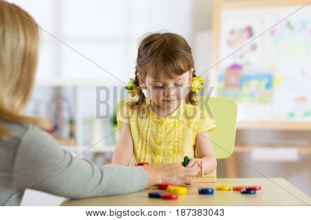 Tutor and preschooler kid playing with educational toys in daycare