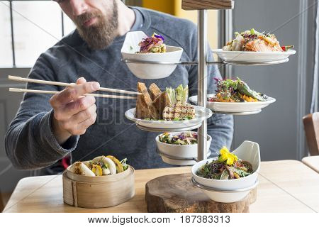 Man Takes Tofu From Tiered Plate Server In Restaurant