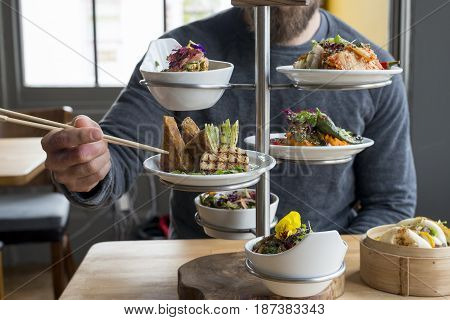 Man Picking Tofu From Tiered Server Using Chopsticks