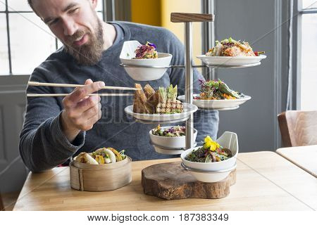 Dining Customer Takes Tofu Using Chopsticks From Tiered Server