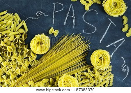 Different types of dried Italian pasta on a blue background. Top view with chalk written pasta