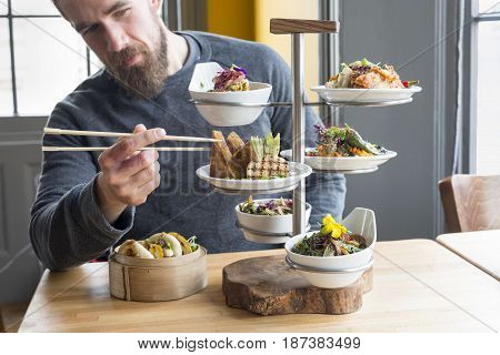 Man Takes Tofu Using Chopsticks From Tiered Server In Restaurant