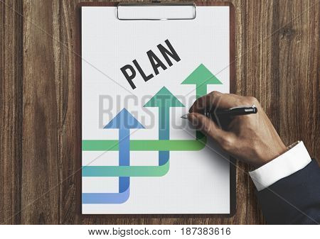 Hands Writing Business Plan on the Sheet