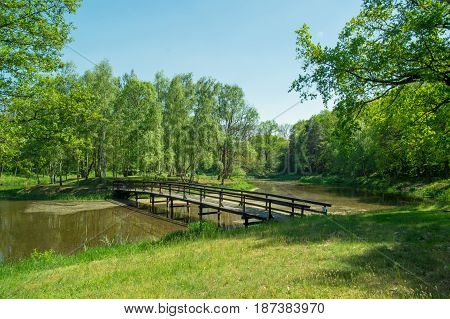 The photo shows a small bridge, a wooden footbridge connecting the island's overgrown island. The footbridge runs over the surface of the lake. It is sunny day.