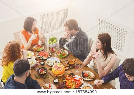 Friends meeting. Group of happy people talking, eating, passing healthy meals at party dinner table in cafe, restaurant. Young company celebrate with alcohol and food at wooden table indoors.