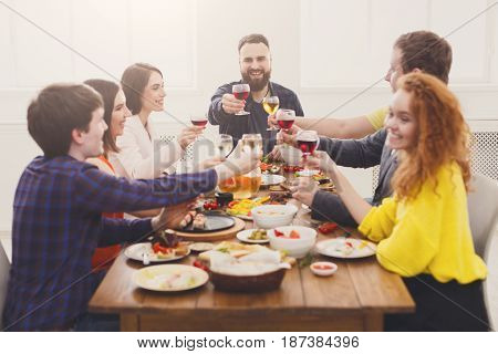 People drink wine, clink glasses, saying cheers at party dinner table in cafe, restaurant or at home. Young cute friends company celebrate with organic food at wooden table indoors.