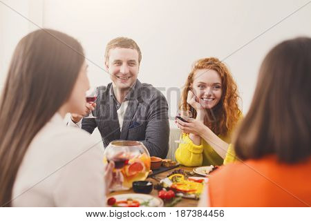 Happy couple celebrate with friends, have dinner in restaurant or at home party. People have meals together, friendly conversation