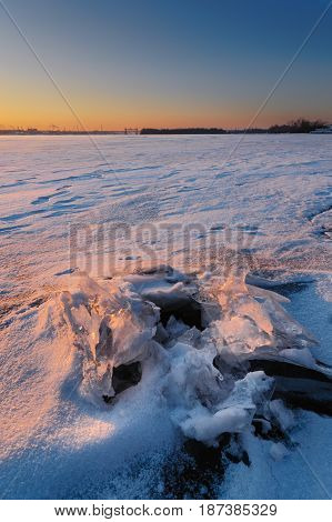 Bank of the river in the rays of a bright sun at sunset in winter. Ukraine, Dnepr