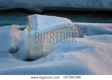 A beautiful epic ice crystal on the snow in the rays of the setting sun.