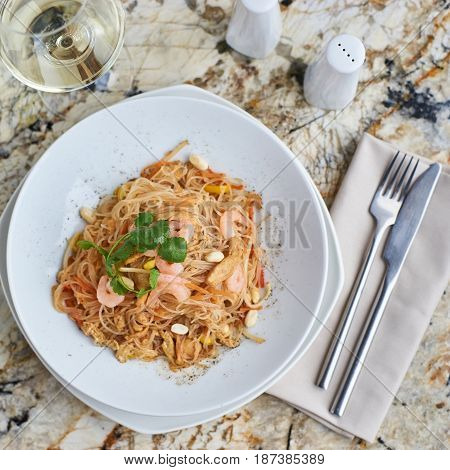 Rice noodles with peanuts, chicken and shrimps served on white round plate with glass of white white on marble table