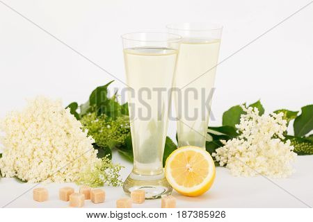 Glasses of healthy juice, elderberry flowers and lemon, alternative medicine and therapy