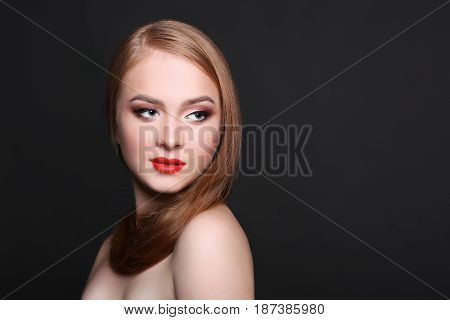 Beauty model on black background, fashion shooting. Woman with makeup, perfect skin and hair posing to camera at studio, copy space