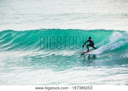 Surfing in turquoise barrel in ocean. Big wave and surfer