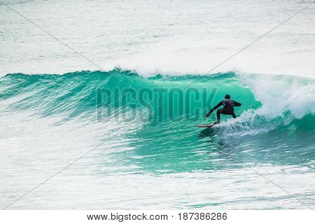 Surfing in turquoise barrel in ocean. Surfer on wave