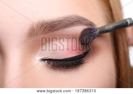 Eyeshadow applying, makeup for eyes closeup. Female model face with fashion make-up, beauty concept isolated