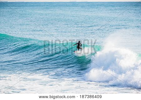 Surfing on turquoise wave in ocean. Surfer in wet suit