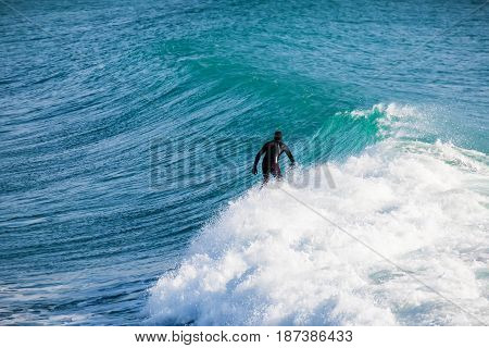 Surfing and beautiful blue wave in ocean.