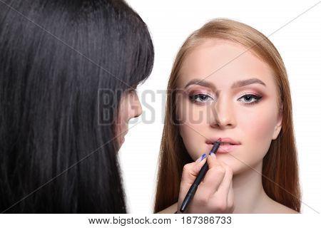 Make-up artist applying lipstick makeup for beauty model, isolated on white background