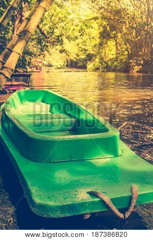 Plastic green rowboat and calm river with bamboo trees on nature background vertical view. Outdoor at the daytime on summer day with bright sunlight. Cross process and vintage effect tone.