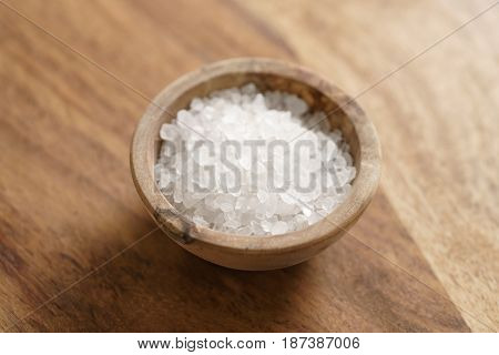 coarse sea salt in wooden bowl on table, close up