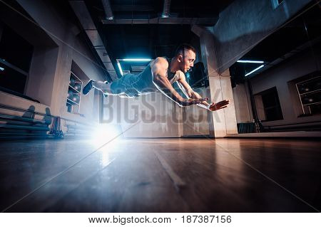 Attractive Muscular Man Doing Push-ups On A Wooden Floor.
