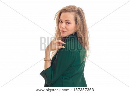 Portrait of a beautiful young blonde in a green jacket that stands sideways and turned her head to the camera isolated on white background