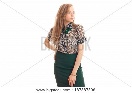 beautiful young blonde girl in blouse and skirt posing on camera by unscrewing the head towards isolated on white background