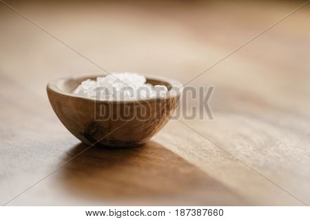 coarse sea salt in wooden bowl on table, with copy space