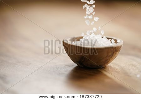 coarse sea salt falling in wooden bowl on table, with copy space