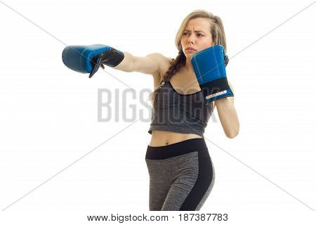 beautiful young girl with a scythe in a gray sports suit make in boxing gloves is isolated on a white background