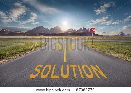 Crossing with stop sign and arrows towards the sun and mountain peaks with yellow line and solution text on asphalt. Success and vision concept.