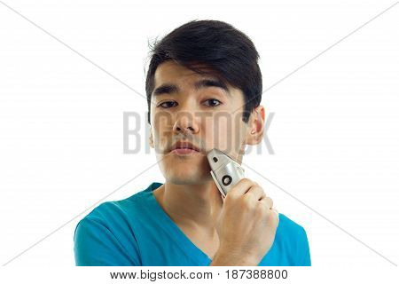 Portrait of an amazing young guy who looks straight and shaves machine is isolated on a white background